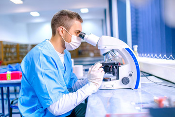 Male scientist, chemist working with microscope in laboratory