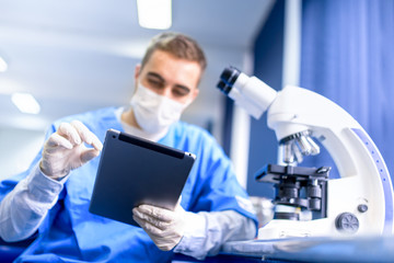 man working on prescription with modern tablet and microscope