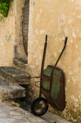 Old wheelbarrow is positioned against a stone.