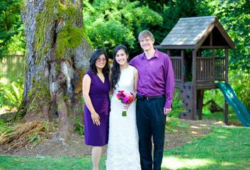 Beautiful biracial bride standing with her parents. Diversity.