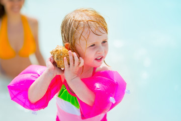 Baby girl in inflatable armband listening sound of sea in shell