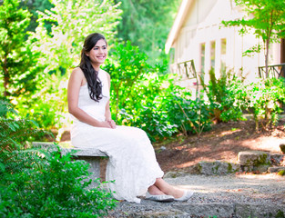Beautiful biracial bride in white lace wedding dress sitting on