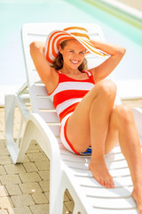 Smiling young woman in hat laying on sunbed