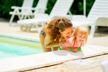 Portrait of mother and baby girl playing in pool