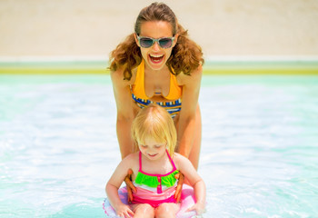 Happy mother and baby girl playing in pool