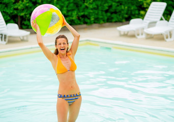 Portrait of smiling young woman with beach ball