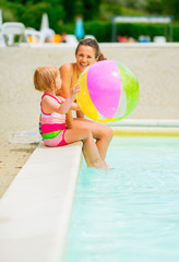 Mother and baby girl with beach ball at poolside
