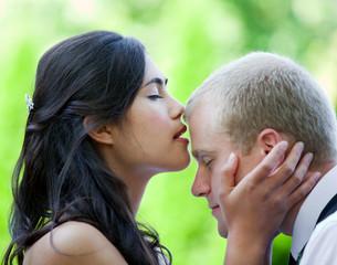 Biracial bride kissing Caucasian groom on forehead.