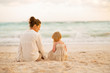 Mother and baby girl sitting on beach at the evening. rear view
