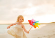 canvas print picture - Baby girl playing with colorful windmill toy on beach