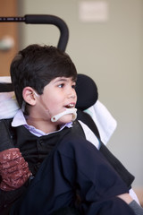Handsome disabled eight year old biracial boy smiling and relaxi