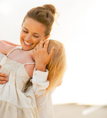 Portrait of mother and baby girl hugging on beach at the evening