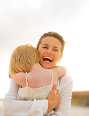 Portrait of smiling mother and baby girl hugging on beach