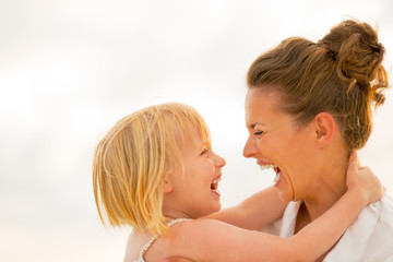 Portrait of laughing mother and baby girl hugging on beach