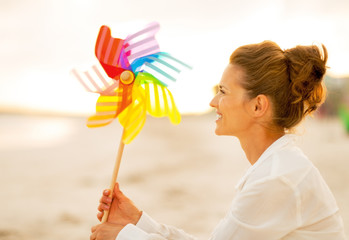 Happy young woman with colorful windmill toy sitting on beach