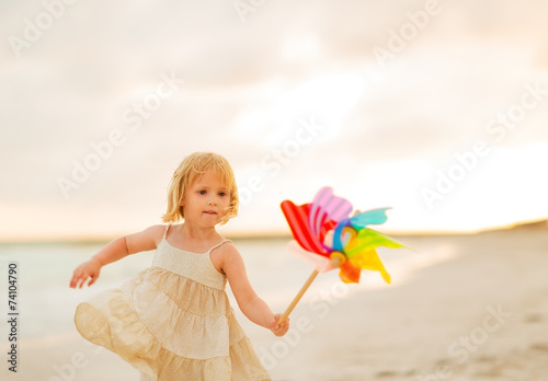 canvas print picture Baby girl playing with colorful windmill toy on beach