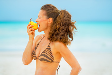 Happy young woman eating pear on beach