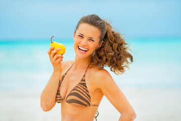 Portrait of smiling young woman with pear on beach
