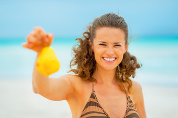 Portrait of smiling young woman showing pear while on beach