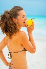 Young woman eating pear on beach