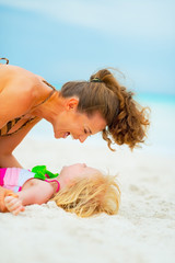 Laughing mother and baby girl playing on beach