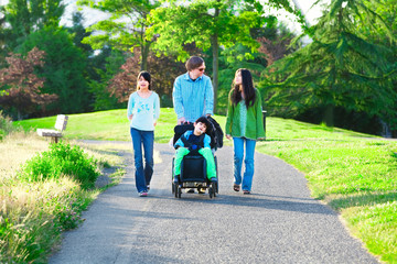 Disabled boy in wheelchair walking with family outdoors on sunny