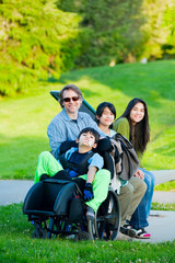 Disabled boy in wheelchair with family outdoors on sunny day sit