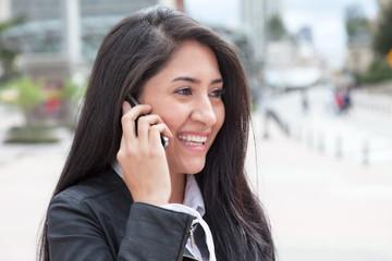 Frau mit langen schwarzen Haaren am Handy in der Stadt