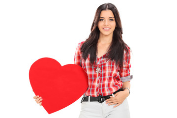 Attractive female holding a red heart symbolizing love