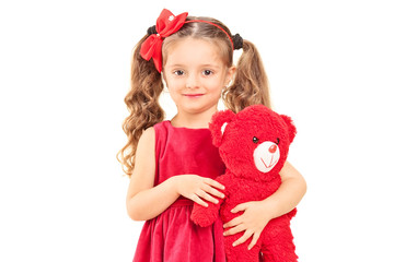 Cute little girl holding a red teddy bear