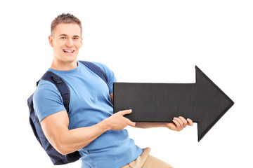 Male student holding a big black arrow pointing right