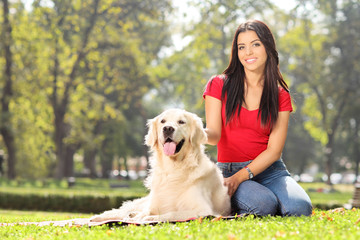 Girl sitting in park with her dog