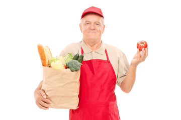 Mature market vendor holding a grocery bag