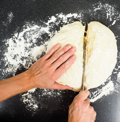 Hands cutting a lump of dough into two pieces