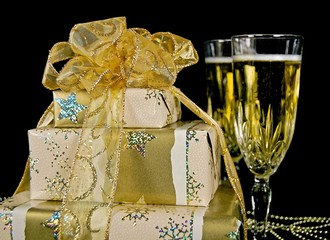 gold Christmas gifts with champagne flutes