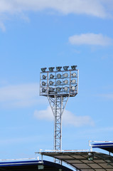 Single spot-light pole with blue sky in stadium