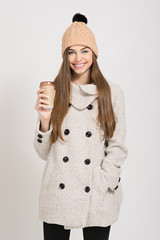 Fashionable girl in coat and beanie with takeaway coffee