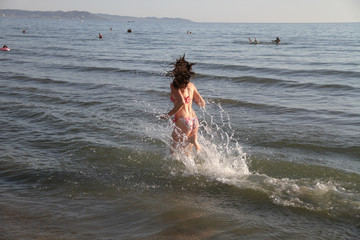 Young attractive woman running along the seashore