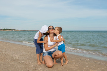 Mother and her two sons having fun on the beach
