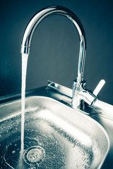 mixer tap with flowing water, blue tone