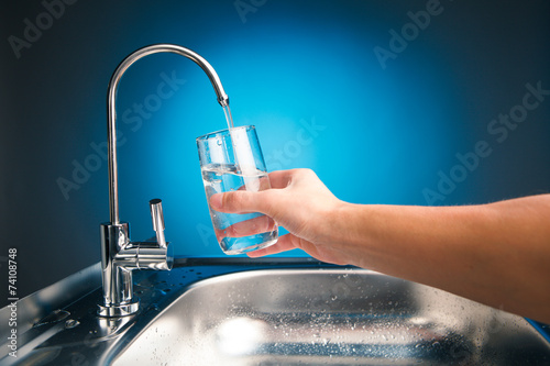 canvas print picture hand pouring a glass of water from filter tap