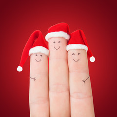 Fingers faces in Santa hats against red background. Happy family