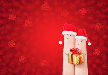 Fingers faces in Santa hats with gift box. Happy couple celebrat