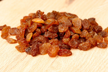 Raisins on wood plank, background