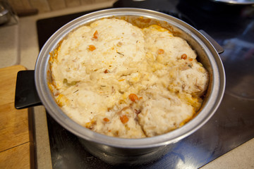 Thick dumplings in a turkey stew cooking on a stove top.