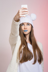 Teenage girl with beanie and blue lipstick taking a selfie