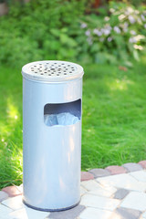 Trash can in park on green grass background