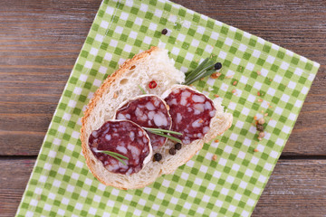 Sandwich with salami on napkin on wooden background