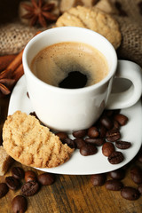 Cup of espresso and tasty cookie on wooden background