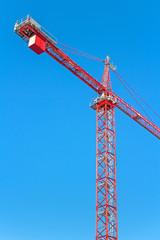 Construction tower crane against clear blue sky, vertical